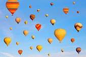 Vibrant colorful air balloons in blue sky.