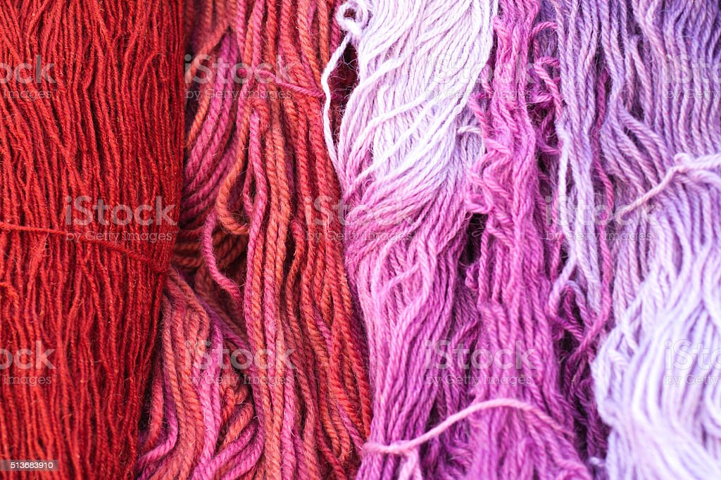 Vibrant Colorful Pink, Purple and Red Hanging Yarn (Full Frame) stock photo