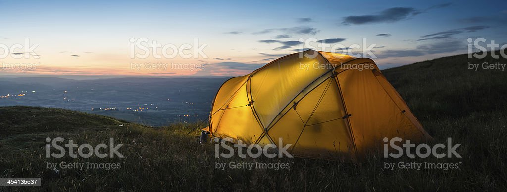 Vibrant dome tent on mountain overlooking sunset lights in valley royalty-free stock photo