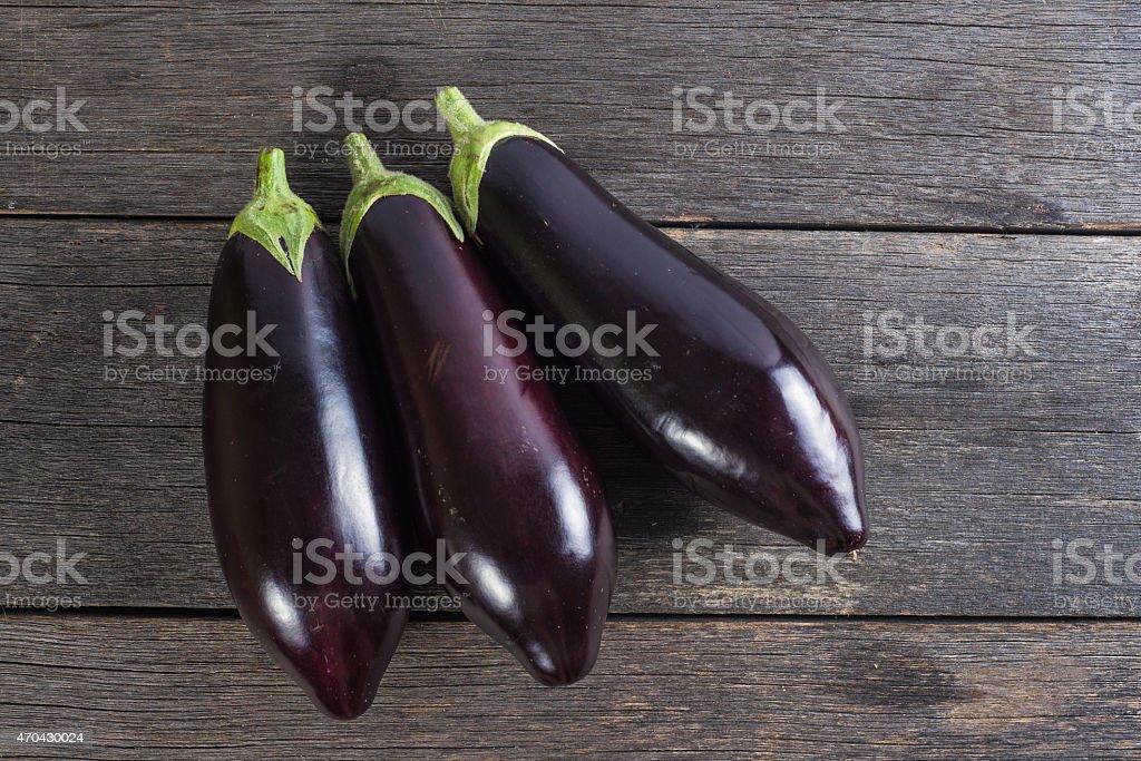 Vibrant fresh aubergine on wooden table stock photo