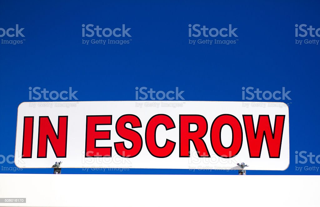 Vibrant 'In Escrow' Sign Against Blue Sky stock photo