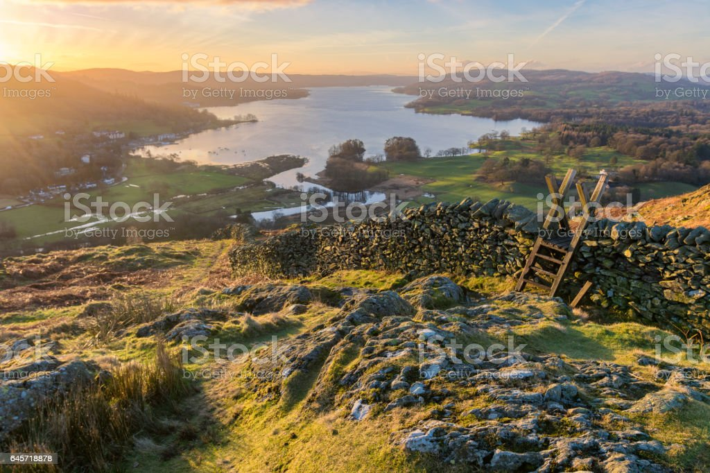 Vibrant Lake District Sunrise With Wall And Stile. stock photo