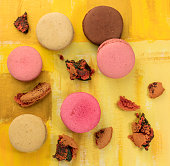 Vibrant macarons with crumbs on bright yellow texture
