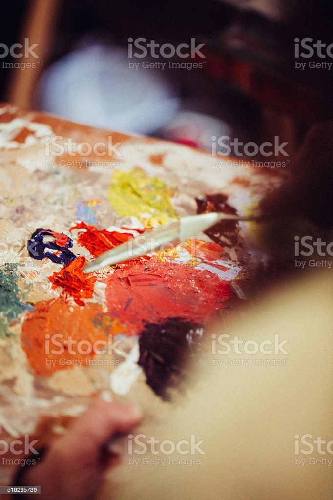 Vibrant multi colored paints on a palette mixed with knife stock photo