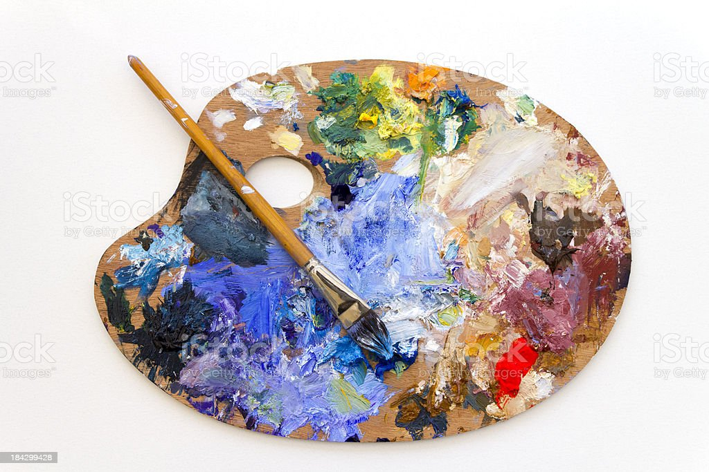Vibrant multi-coloured artists traditional wooden oil paint palette and brush stock photo