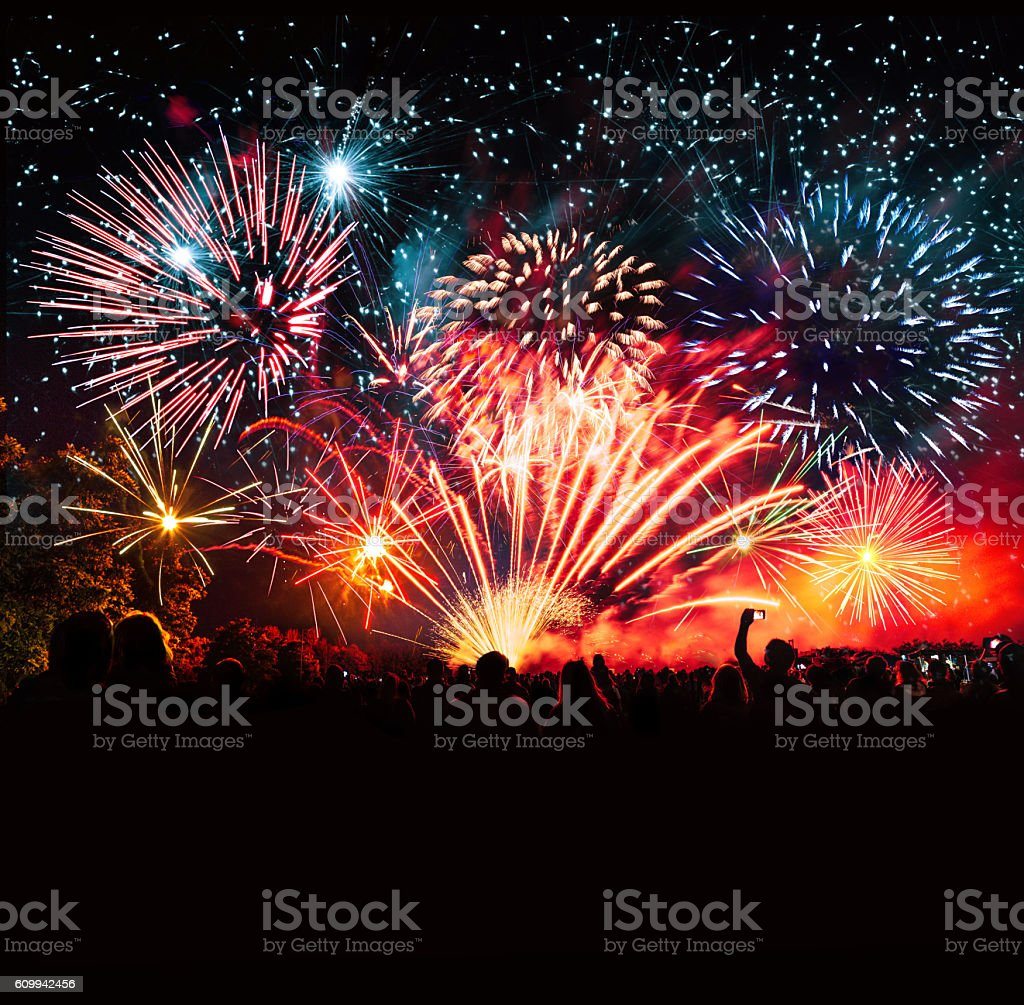 vibrant new years banner with  fireworks and cheering crowd stock photo