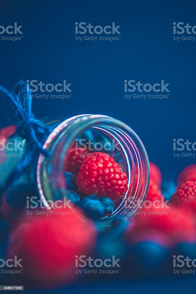 Vibrant organic raspberries and blueberries spilling from glass jar stock photo