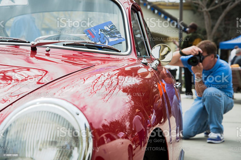 Vibrant Signal Red Porsche 356C with a Photographer in Background stock photo