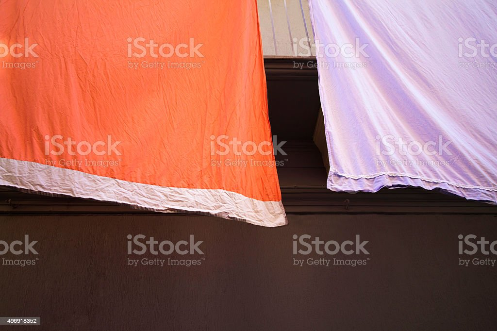 Vibrant (Orange and Purple) Sunlit Sheets Hanging Against Black Background stock photo