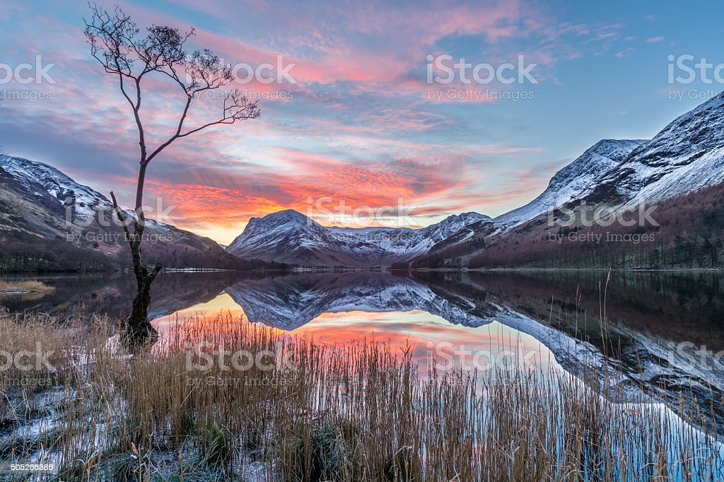 Vibrant Sunrise At Buttermere With Reflections And Snow On Mountains. stock photo