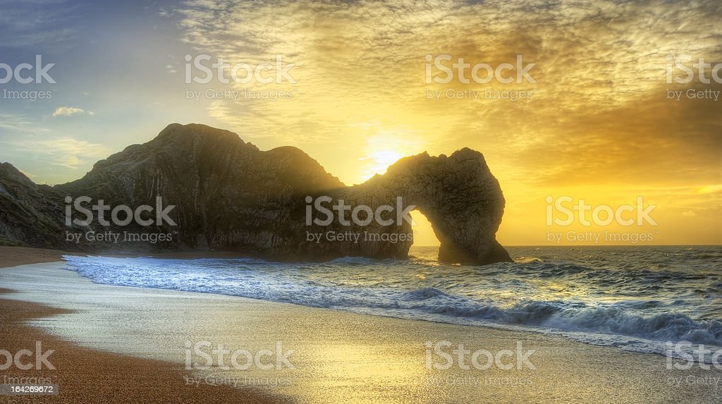 Vibrant sunrise over ocean with rock stack in foreground royalty-free stock photo