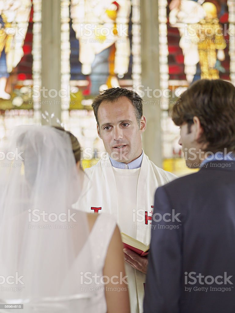 Vicar marrying young couple royalty-free stock photo