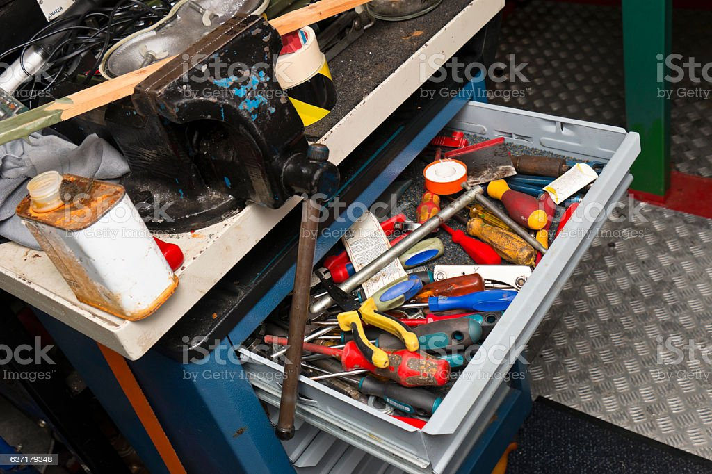 Vice and messy workbench with Toolbox stock photo