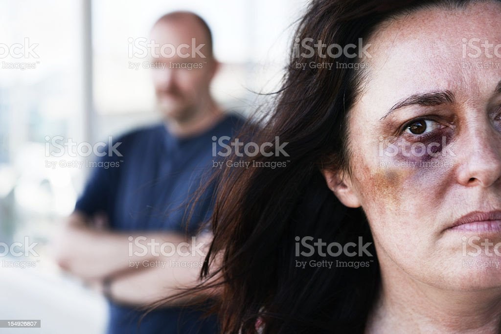 Victim of domestic violence with threatening man in background stock photo