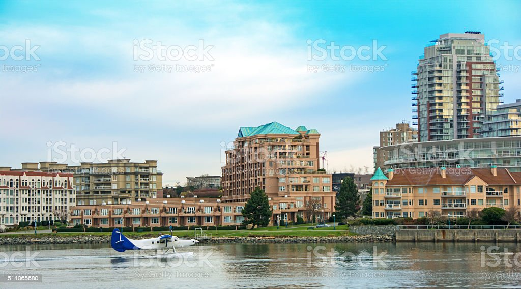 Victoria harbor commericial sea plane just after landing- condos background stock photo
