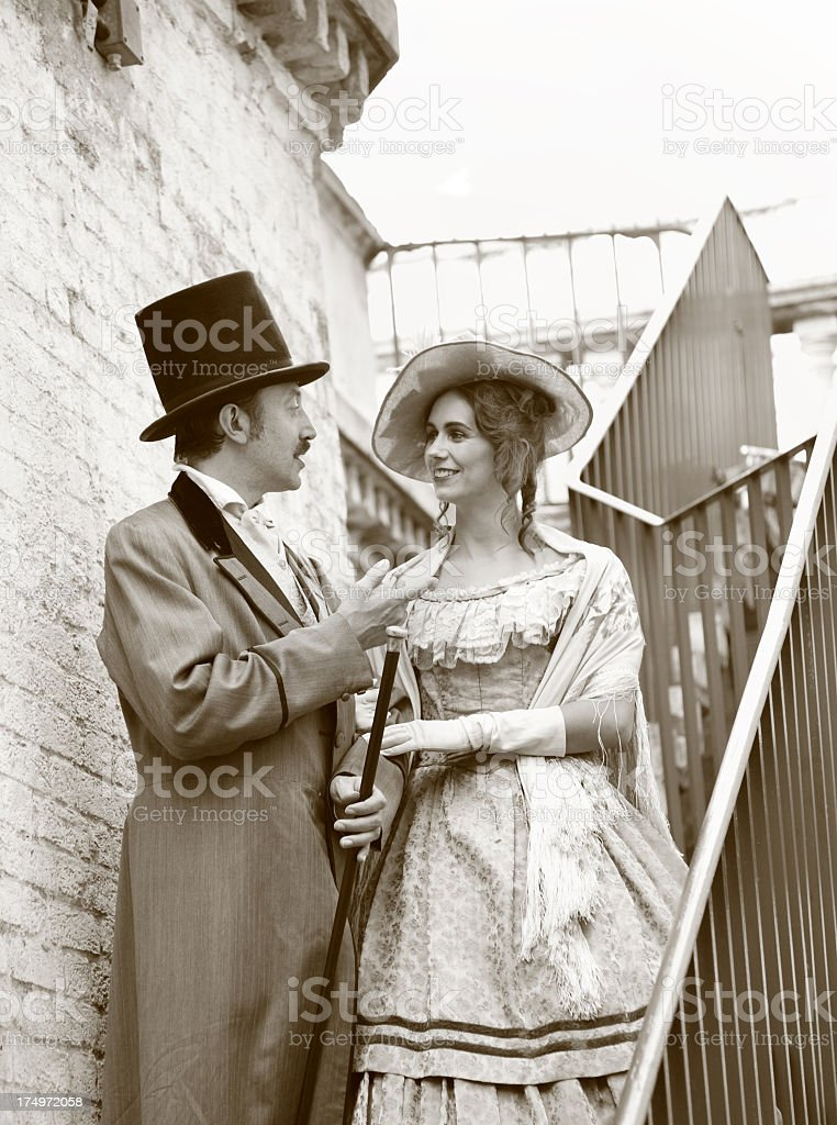 victorian gentleman and lady chat on iron stairway stock photo