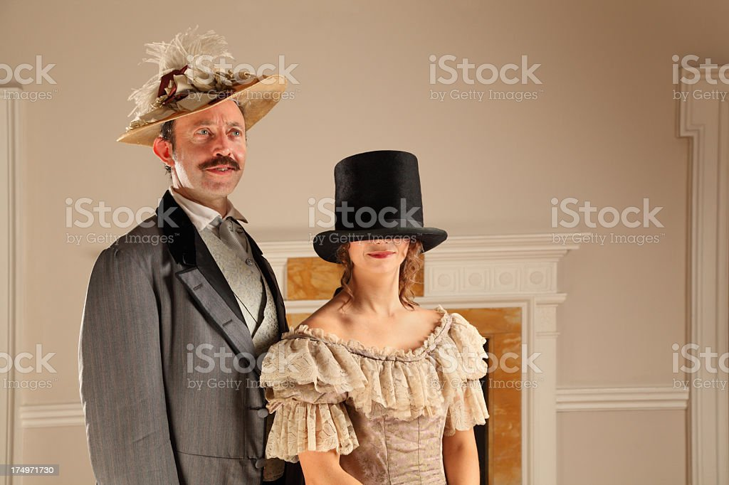 Victorian man and wife in funny formal dress pose stock photo