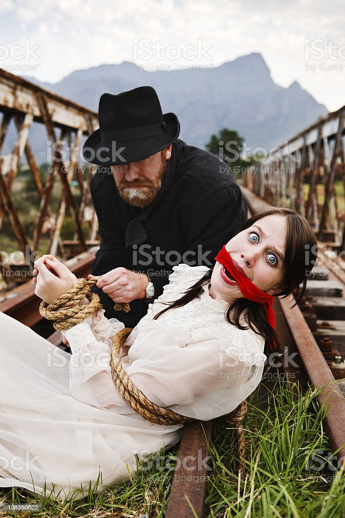 Victorian melodrama as villain ties terrified maiden to railway track royalty-free stock photo