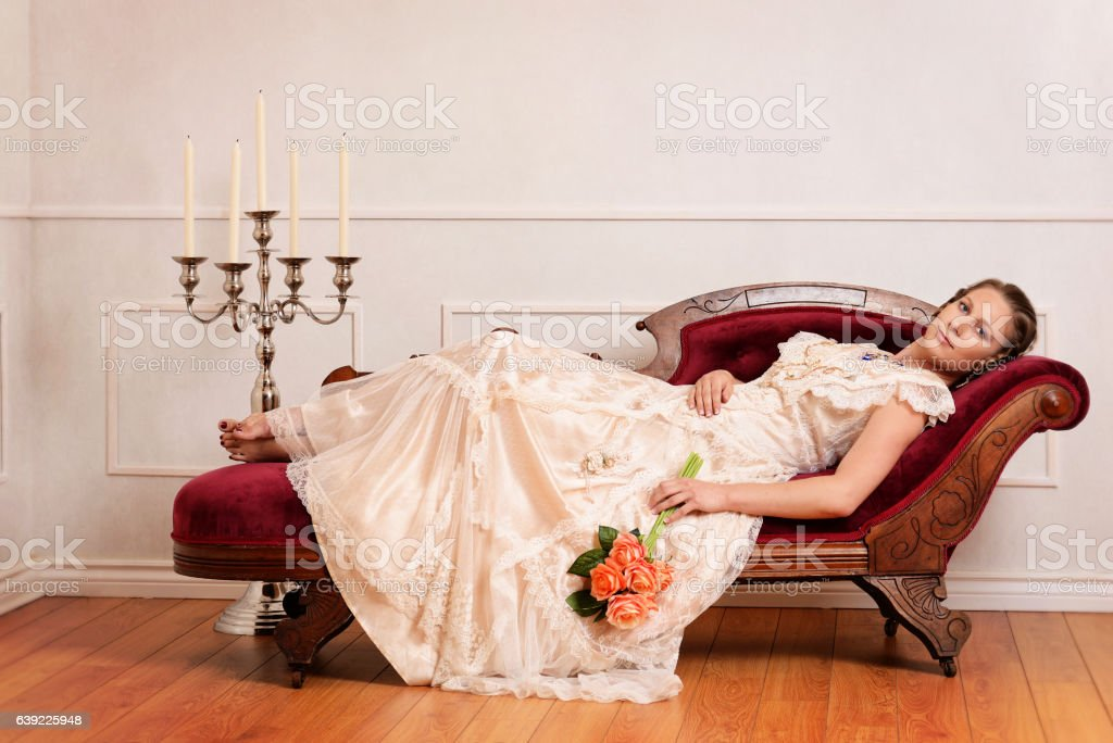 victorian woman on couch with orange roses stock photo