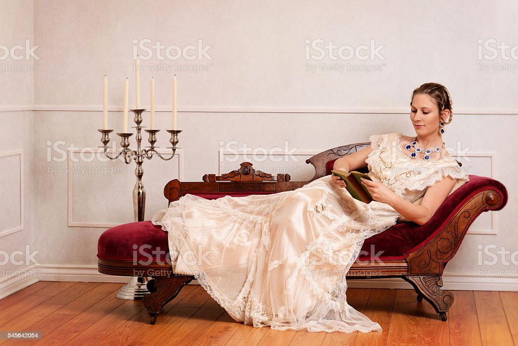 victorian woman reading book on fainting couch stock photo