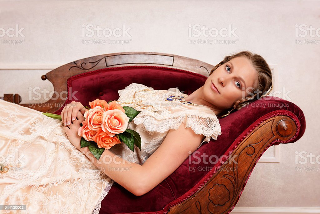 victorian woman with flowers on fainting couch stock photo