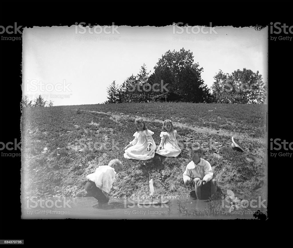 Victorian-era Children Playing with a Toy Boat stock photo