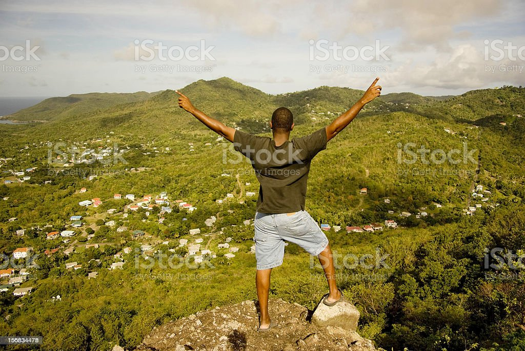 victorious above all, man on mountaintop looking down at village royalty-free stock photo