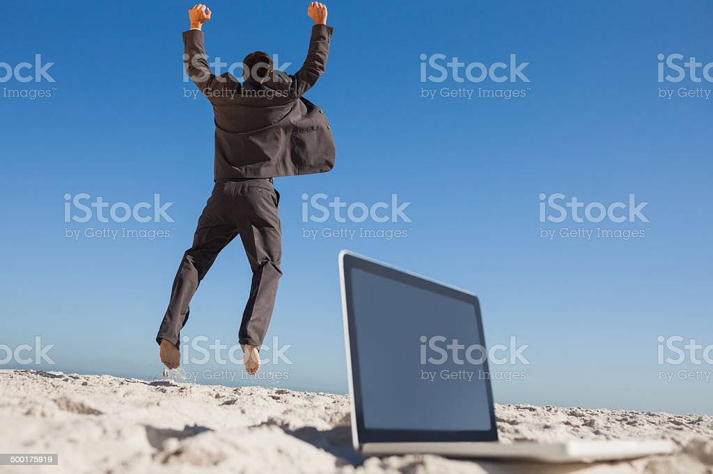 Victorious businessman jumping leaving his laptop stock photo