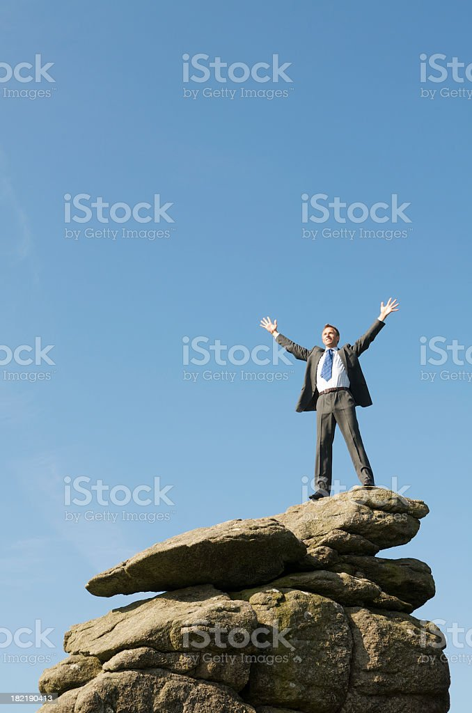 Victorious Businessman Standing Outdoors on Top of Rock royalty-free stock photo