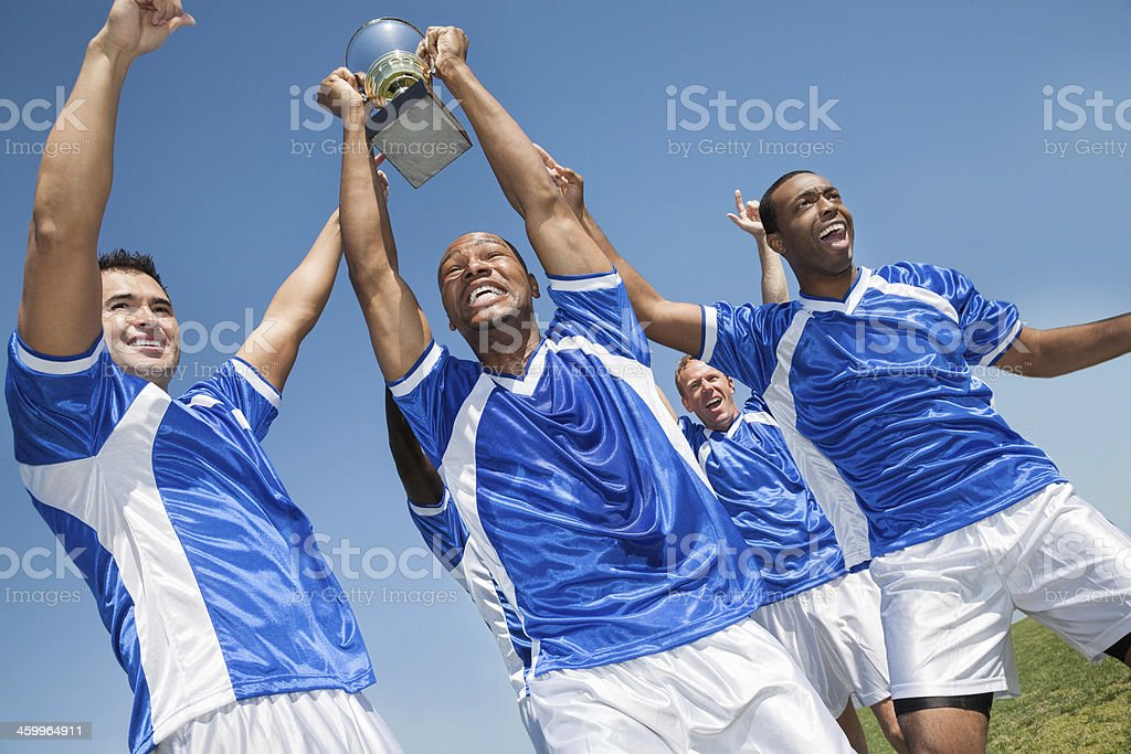 Victorious soccer team holding trophy and celebrating win royalty-free stock photo