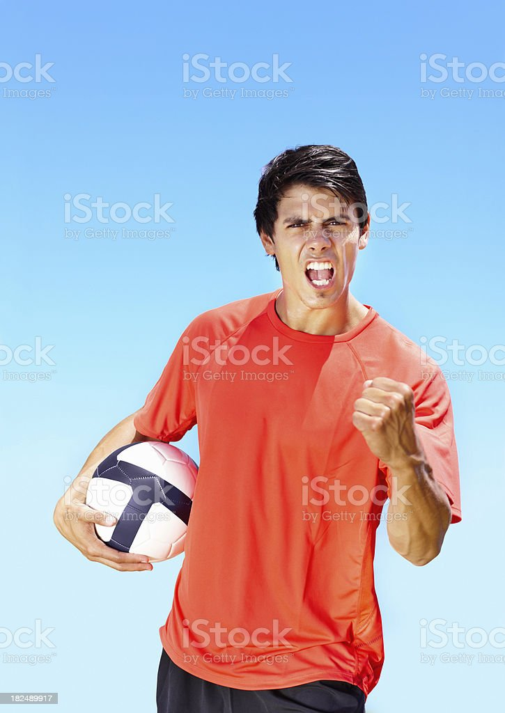 Victorious young footballer holding a football royalty-free stock photo