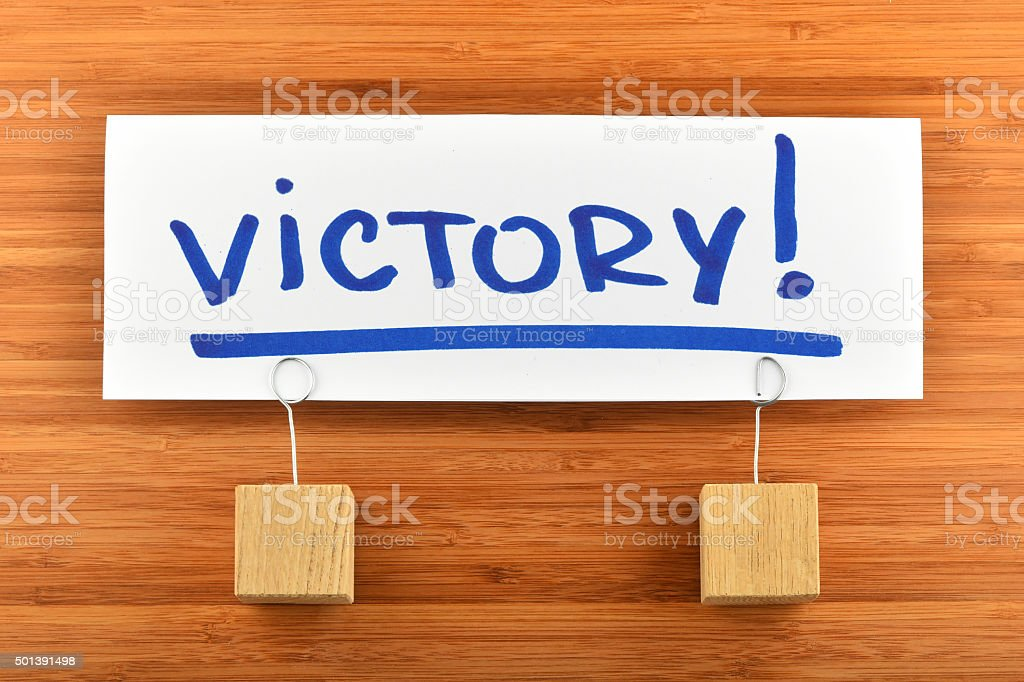 Victory paper note with  holders on wooden background royalty-free stock photo