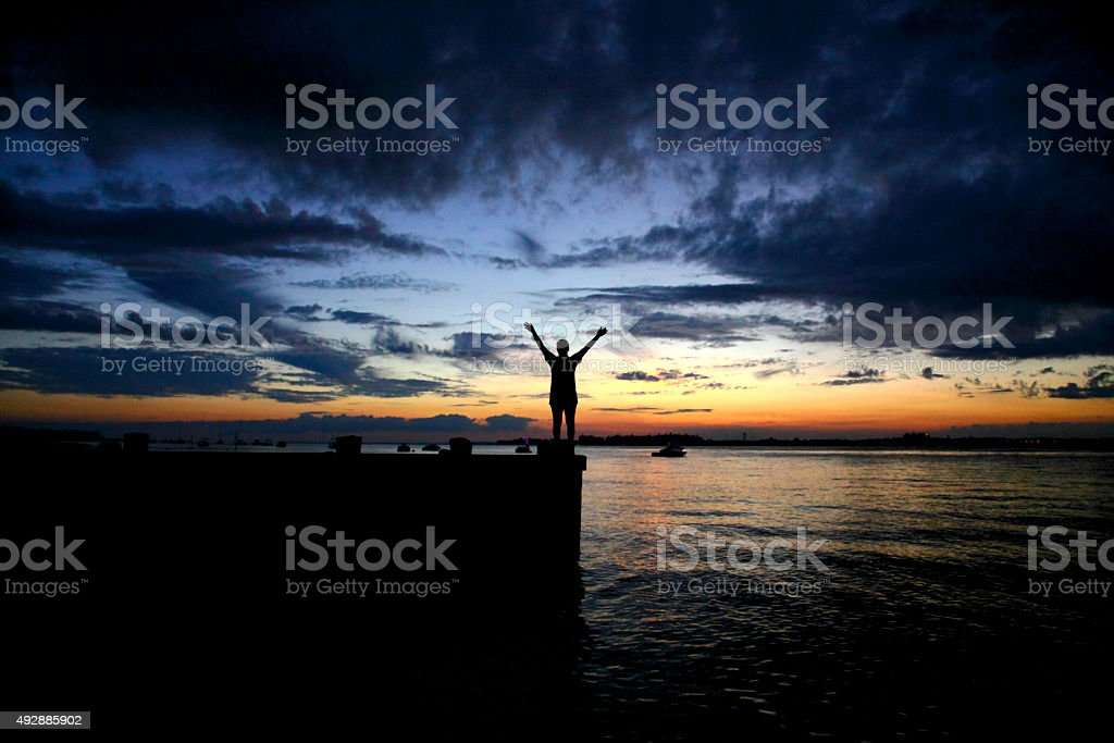 Victory silhouette against a beach background at sunset stock photo