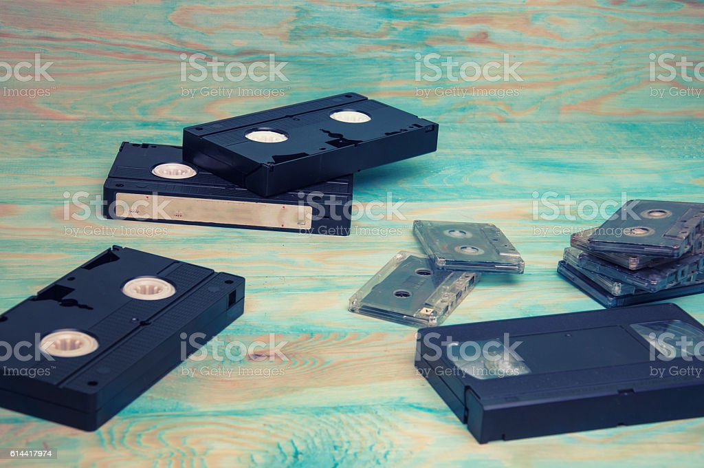 Video and music tapes on blue wooden background stock photo