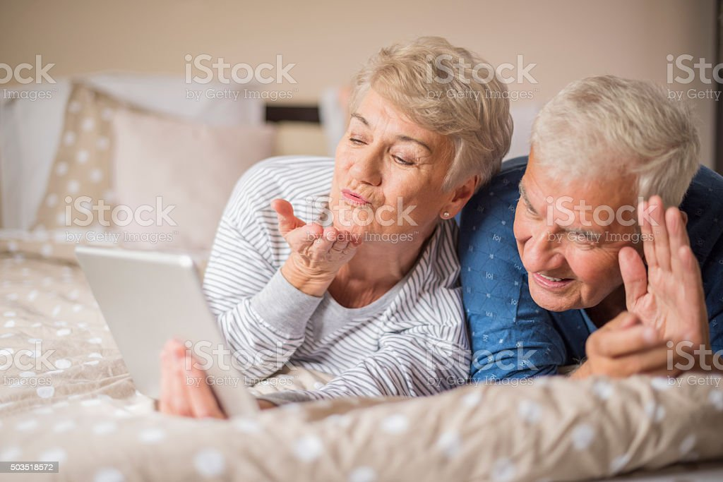 Video conference of cheerful senior couple stock photo