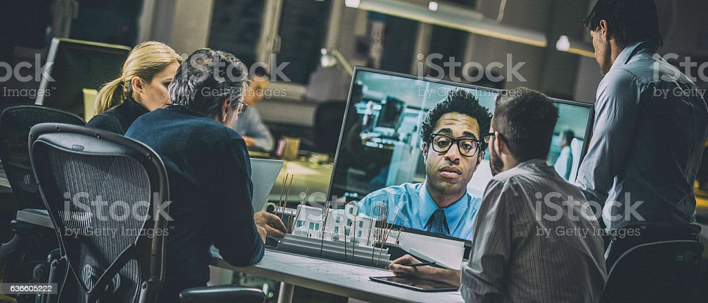 Video conference with businessman talking to architects stock photo