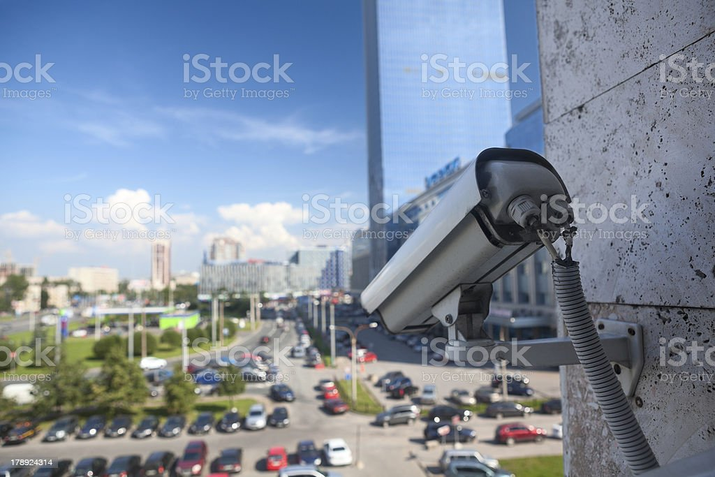 Video surveillance camera on wall looking at street parking zone royalty-free stock photo