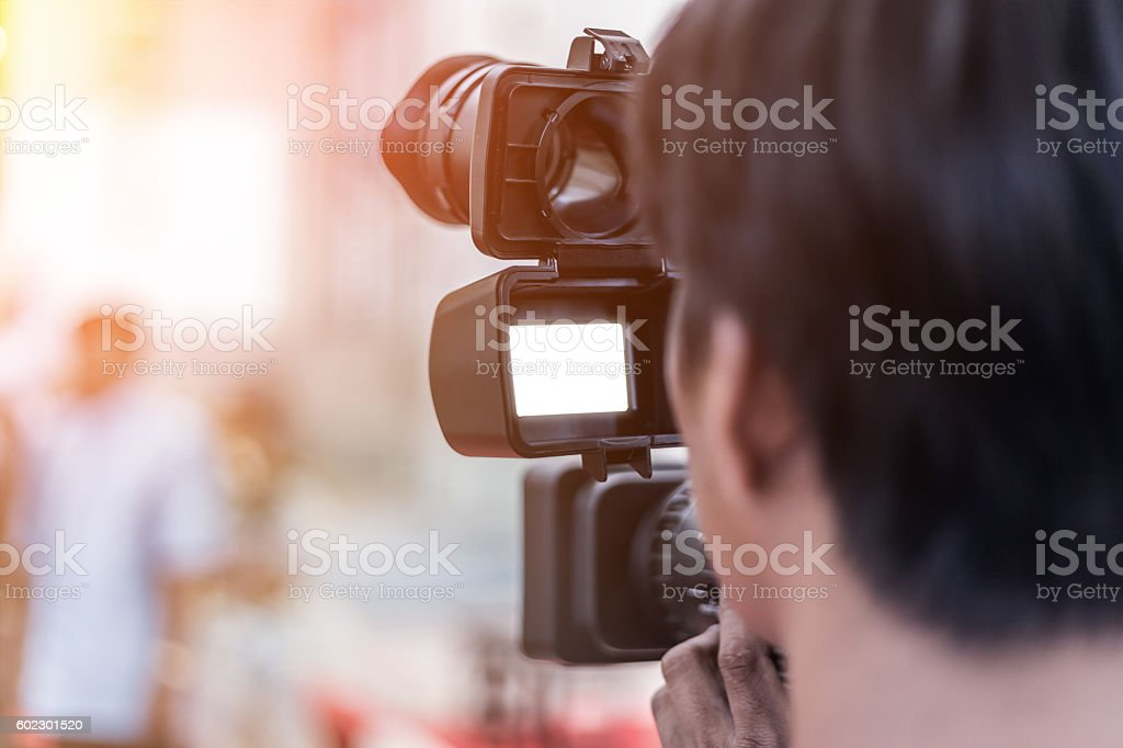 Videographer takes video camera stock photo
