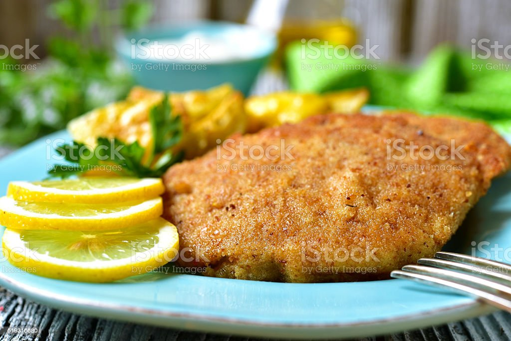 Viennese schnitzel on a blue plate. stock photo
