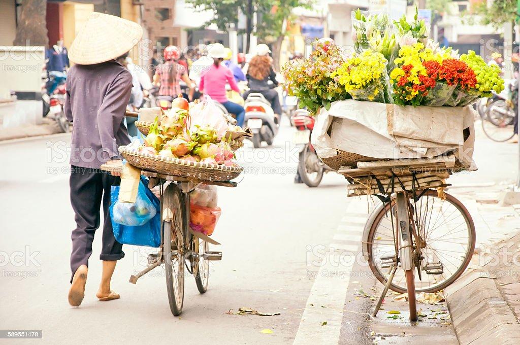 Vietnam florist vendor on bicycle on street in Hanoi. stock photo