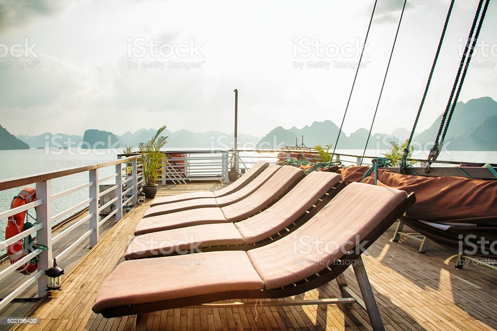 Vietnam Halong Bay Cruise ship top deck with lounging chairs stock photo