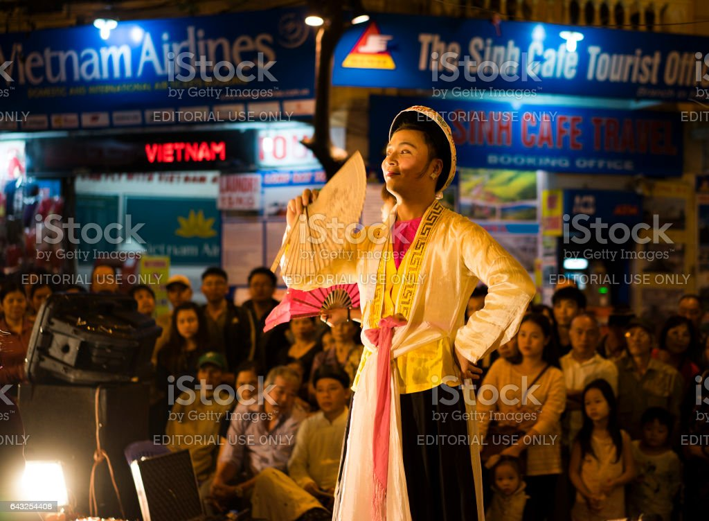 Hanoi, Vietnam - Nov 2, 2014: Vietnamese artists perform folk music and song on Ma May st, old town of Hanoi. The male artist plays the Holy Mother stock photo
