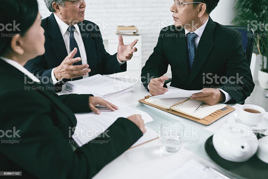 Vietnamese attorneys discussing documents before trial stock photo