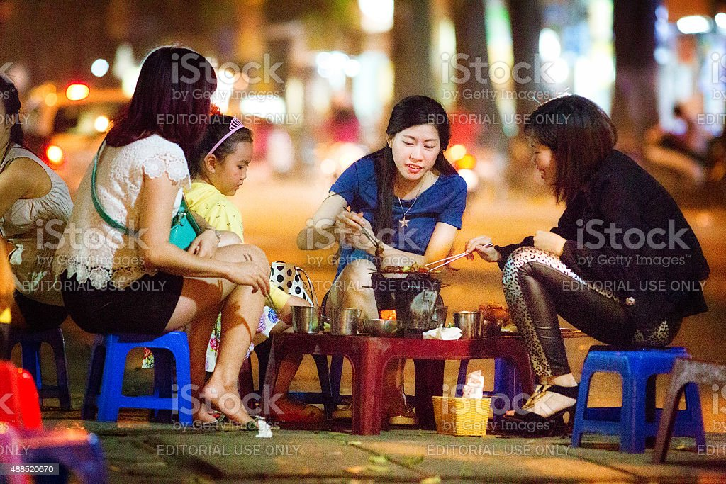 Vietnamese female friends enjoying late night barbecue on Hanoi street stock photo