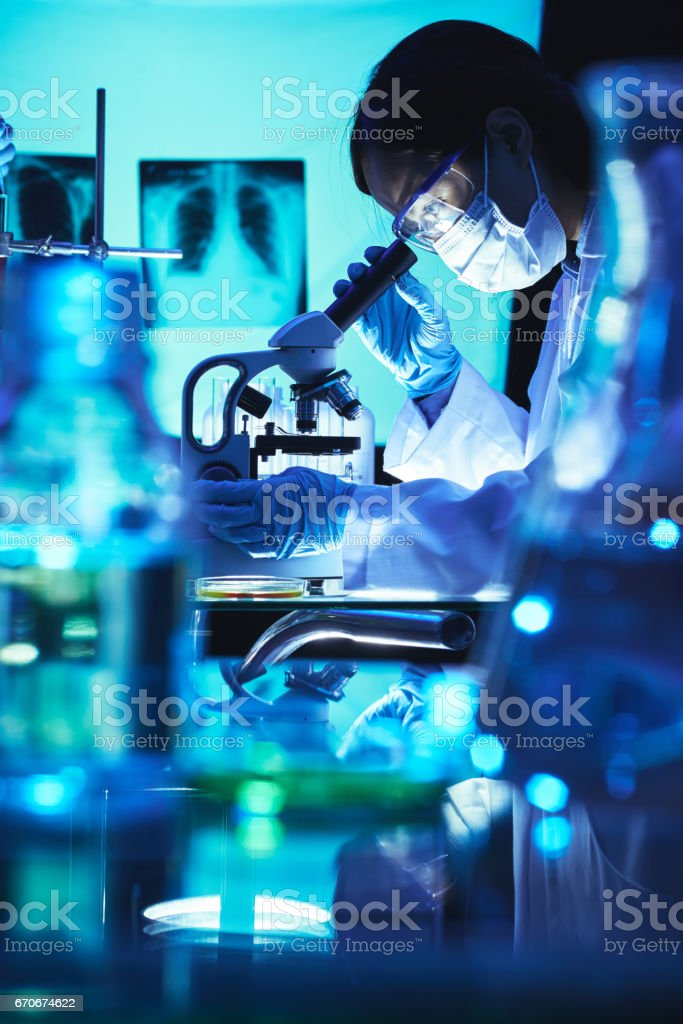 Vietnamese female scientist working with microscope in dark laboratory stock photo
