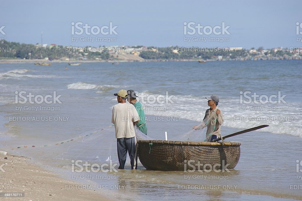 Vietnamese fishermen in a round boat on Mui Ne beach royalty-free stock photo