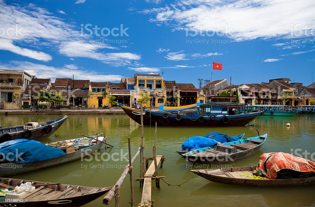 Vietnamese fishing boats and ancient city of Hoi An, Vietnam stock photo