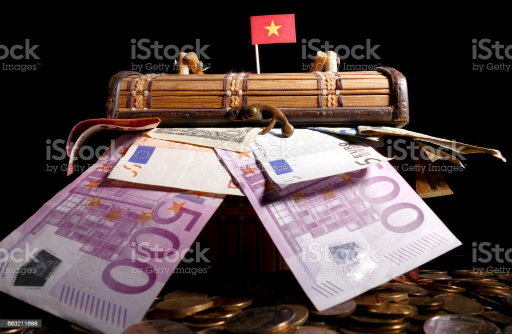 Vietnamese flag on top of crate full of money stock photo