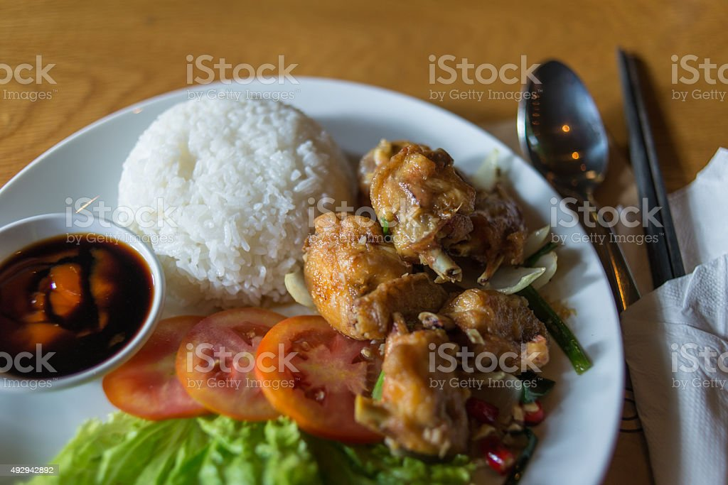Vietnamese fried chicken wings served with rice and salad stock photo