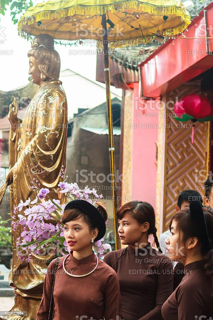 Vietnamese Girls in Ao Dai in front of Guanyin statue stock photo